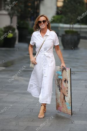 Stock Picture of Amanda Holden holding a picture of herself at Global House radio