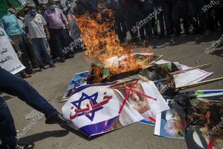 "Palestinians burn pictures of U.S. President Donald Trump, Israeli Prime Minister Benjamin Netanyahu, Bahrain's King Hamad bin Isa Al Khalifa and and Abu Dhabi Crown Prince Mohammed bin Zayed al-Nahyan, during a protest against the United Arab Emirates and Bahraini normalization agreement with Israel, in Gaza City, . Israel is set to sign agreements with the UAE and Bahrain at the White House on Tuesday. Arabic on poster with representation of an Israeli flag reads, ""traitor"