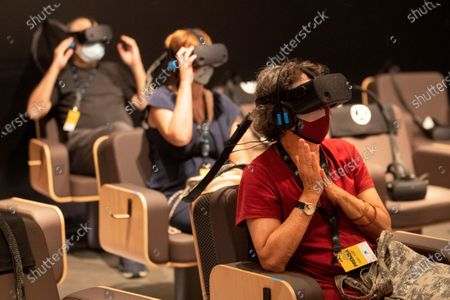 People experience 'Symphony. Un viaje virtual al corazon de la musica' (lit.: Symphony. A virtual journey to the heart of the music) by Venezuelan conductor and director of the Los Angeles Philharmonic orchestra Gustavo Dudamel (unseen) during the presentation in Barcelona, Spain 15 September 2020. The virtual reality project takes advantage of the new technologies to listen classic mussic as if the audience were a part of the orchesta.
