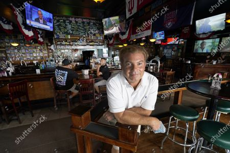"""Stock Photo of Zach Strauss poses at Sluggers World Class Sports Bar, in the Wrigleyville neighborhood of Chicago. The coronavirus pandemic has been especially hard on businesses that rely on ballpark traffic, eliminating crowds at major league games, and leading to rules that limit the amount of people they can have inside their doors at the same time. """"We have no choice but to make it through this,"""" said Strauss, who runs Sluggers with his brothers David and Ari after their father, Steve, opened the bar in 1985"""