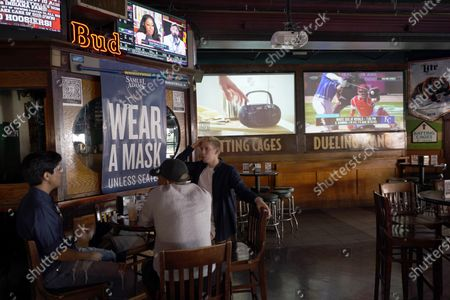 """Stock Image of Patrons at Sluggers World Class Sports Bar, are reminded to wear a mask right along with the sports news of the day in the Wrigleyville neighborhood of Chicago. """"We have no choice but to make it through this,"""" said Zach Strauss, who runs Sluggers with his brothers David and Ari after their father, Steve, opened the bar in 1985"""