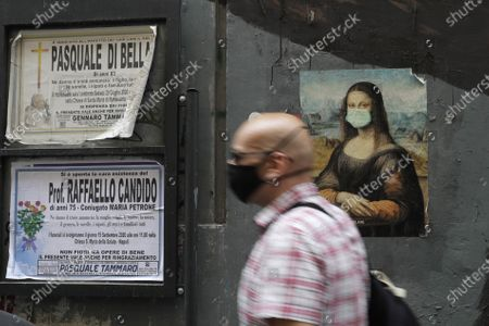 Man walks past a poster of Leonardo Da Vinci's Mona Lisa wearing a surgical mask and some obituaries, in Naples, Italy
