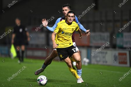 Burton's Ben Fox and Aston Villa's Jack Grealish challenge fo the ball during the English League Cup soccer match between Burton Albion and Aston Villa at Pirelli Stadium in Burton, England
