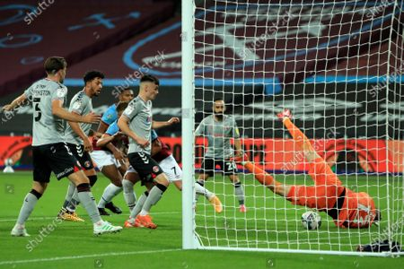Charlton Athletic's goalkeeper Ben Amos, right, dives for a save during the English League Cup soccer match between West Ham United and Charlton Athletic at London stadium in London