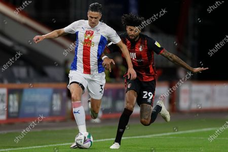 Crystal Palace's Martin Kelly, left, is challenged by Bournemouth's Philip Billing during the English League Cup soccer match between Bournemouth and Crystal Palace at the Dean Court stadium in Bournemouth, England