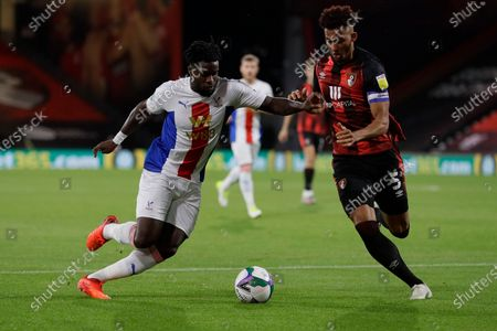 Crystal Palace's Jeffrey Schlupp, left, is challenged by Bournemouth's Lloyd Kelly during the English League Cup soccer match between Bournemouth and Crystal Palace at the Dean Court stadium in Bournemouth, England