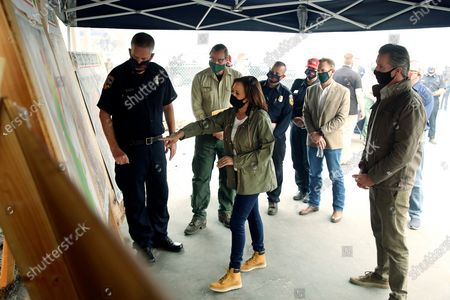 Mark Johnson, left, unit chief for Cal Fire in Fresno, watches Democratic vice presidential candidate Sen. Kamala Harris, D-Calif., and California Gov. Gavin Newsom are briefed on the damage during the Creek Fire at Pine Ridge Elementary, in Auberry, Calif