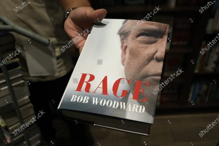 An employee at Shakespeare & Co. holds out the new book by Bob Woodward 'Rage', in New York, New York, USA, 15 September 2020. The book is released after recordings during interviews with US President Donald J. Trump became public, in which he recognized that he underestimated intentionally the gravity of the coronavirus pandemic.