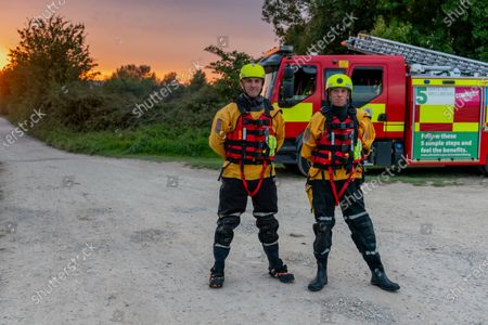 Firefighters Chris Johnson and Paul Greathead from Rewley Road Station, Oxon Fire & Rescue Service, conduct river rescue training activities at dusk.