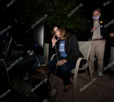 Transgender activist Sarah McBride, who hopes to win a seat in the Delaware Senate, talks on the phone in front of monitors at her watch party in Wilmington, Del