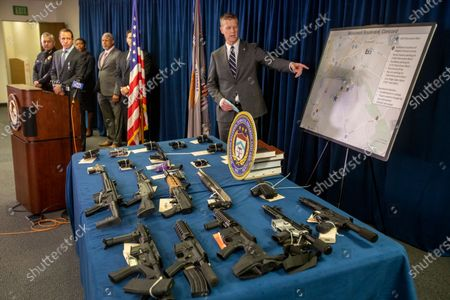 Attorney David L. Anderson announces, the results of a year-long investigation that resulted in the arrest of suspected Sureno gang members and the seizure of firearms during a news conference in San Francisco. On the table is a representative display of similar firearms that was used for illustration. At least 15 suspected gang members have been charged with trafficking drugs and firearms in the San Francisco Bay Area where they used the parking lot of a strip mall for numerous transactions, federal officials announced Tuesday