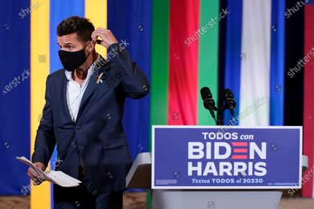 Performer Ricky Martin puts on a mask after speaking at a Hispanic Heritage Month event featuring Democratic presidential candidate former Vice President Joe Biden, at Osceola Heritage Park in Kissimmee, Fla
