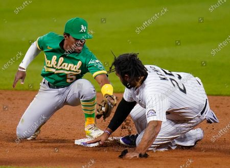 Oakland Athletics' Tony Kemp (5) is late with the tag on Colorado Rockies' Matt Kemp (25) during the sixth inning of a baseball game, in Denver. Kemp advanced on a sacrifice fly by Josh Fuentes