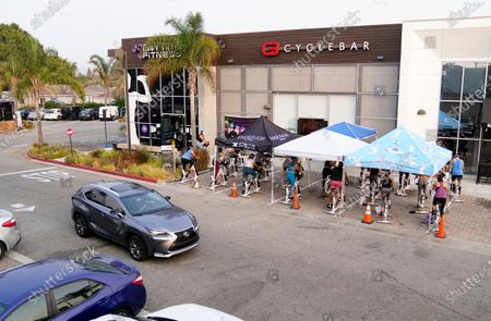 Car rolls past a fitness class taking place in a parking lot outside CycleBar, in Culver City, Calif. California fitness centers have filed a lawsuit alleging Gov. Gavin Newsom's measures aimed at curbing the spread of the coronavirus unfairly target the industry and are demanding they be allowed to reopen