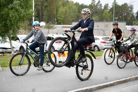 Prince Daniel doing a wheelie while cycling with students during his visit to the British Junior school.