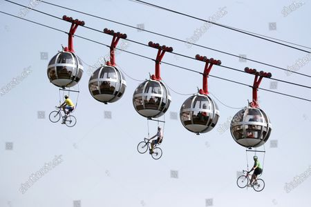 People dressed as riders perform suspended from cable car cabins before the start of the 17th stage of the 107th edition of the Tour de France cycling race over 170 km from Grenoble to Meribel Col de la Loze, France, 16 September 2020.