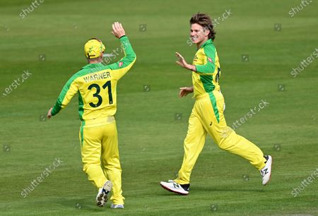 Australia's Adam Zampa, right, celebrates with teammate David Warner the dismissal of England's captain Eoin Morgan during the third ODI cricket match between England and Australia, at Old Trafford in Manchester, England