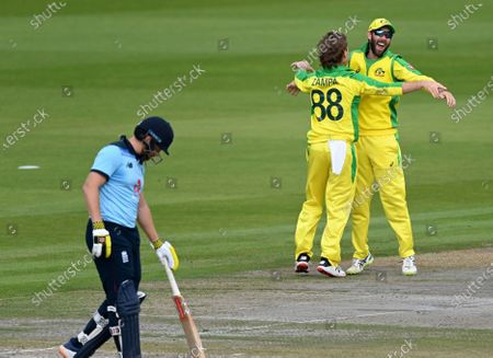 Australia's Adam Zampa, center, celebrates with teammate Glenn Maxwell, right, the dismissal of England's Jos Buttler during the third ODI cricket match between England and Australia, at Old Trafford in Manchester, England