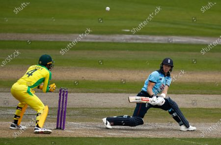 England's Sam Billings, right, plays a reverse sweep during the third ODI cricket match between England and Australia, at Old Trafford in Manchester, England