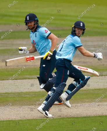 England's Jonny Bairstow, left, and Sam Billings run between the wickets to score during the third ODI cricket match between England and Australia, at Old Trafford in Manchester, England