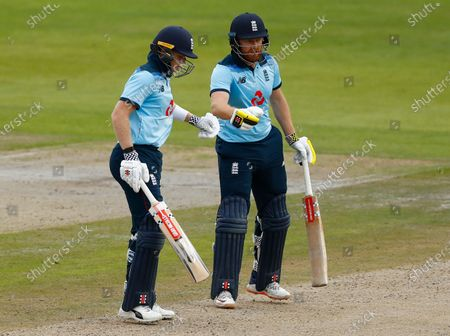 England's Sam Billings, left, celebrates scoring fifty runs with batting partner Jonny Bairstow during the third ODI cricket match between England and Australia, at Old Trafford in Manchester, England