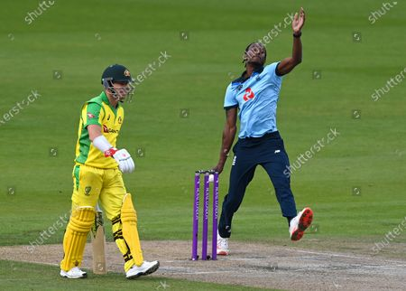 England's Jofra Archer, right, bowls past Australia's David Warner during the third ODI cricket match between England and Australia, at Old Trafford in Manchester, England
