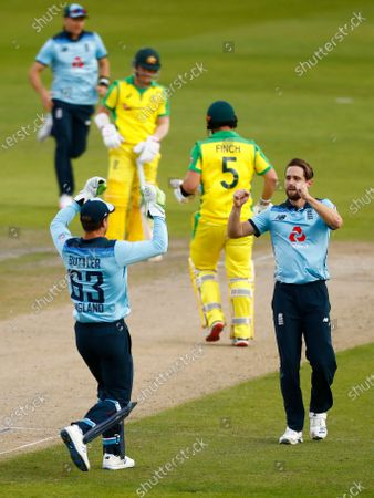England's Chris Woakes, right, celebrates the dismissal of Australia's captain Aaron Finch, second right, during the third ODI cricket match between England and Australia, at Old Trafford in Manchester, England