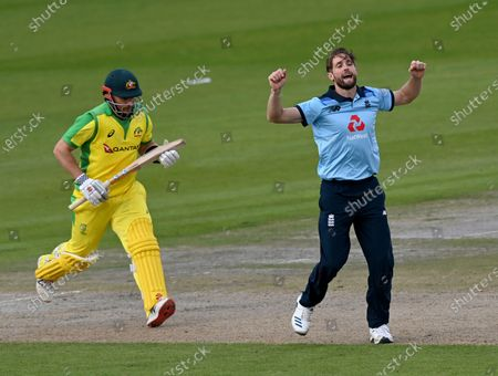 England's Chris Woakes, right, celebrates the dismissal of Australia's captain Aaron Finch, left, during the third ODI cricket match between England and Australia, at Old Trafford in Manchester, England