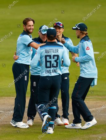 England's Chris Woakes, left, celebrates with teammates the dismissal of Australia's Marcus Stoinis during the third ODI cricket match between England and Australia, at Old Trafford in Manchester, England