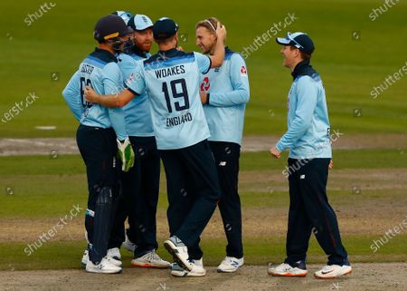 Stock Image of England's Joe Root, second right, is congratulated by teammates after taking the wicket of Australia's David Warner during the third ODI cricket match between England and Australia, at Old Trafford in Manchester, England