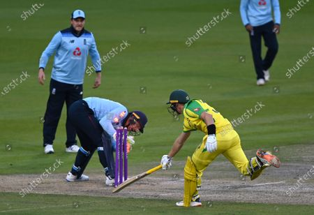 England's wicketkeeper Jos Buttler, center, breaks the stumps to run-out of Australia's Marnus Labuschagne, right, during the third ODI cricket match between England and Australia, at Old Trafford in Manchester, England