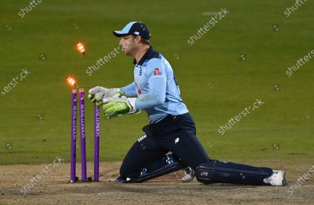 England's wicketkeeper Jos Buttler breaks the stumps in an unsuccessful attempt to run-out Australia's Alex Carey during the third ODI cricket match between England and Australia, at Old Trafford in Manchester, England