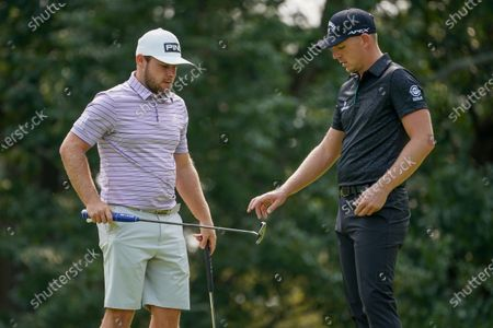 Tyrell Hatton, of England, left, hands a putter to Matt Wallace, of England, during a practice round for the US Open Golf Championship, in New York