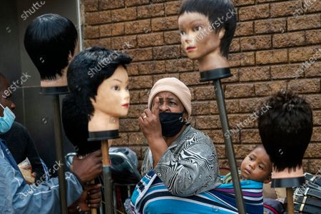 Woman carrying a child on her back looks at wigs on sale at the Baragwanath taxi rank in Soweto, South Africa, . South African president Cyril Ramaphosa is scheduled to address the nation later in the day, as case numbers and death from Covid-19 hit the lowest in months