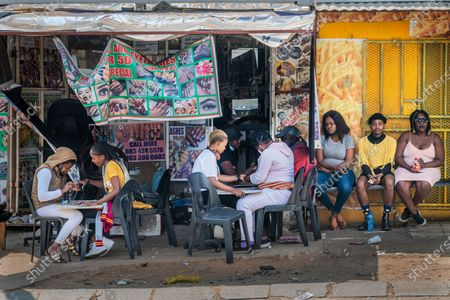 Customers have their nails done near the Baragwanath taxi rank in Soweto, South Africa, . South African president Cyril Ramaphosa is scheduled to address the nation later in the day, as case numbers and death from Covid-19 hit the lowest in months