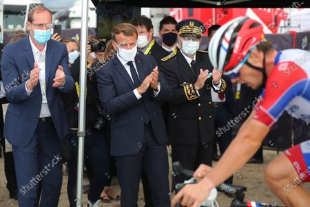 French President Emmanuel Macron, center, and Tour de France director Christian Prudhomme, left, applaud a rider at the Col de la Loze during the stage 17 of the Tour de France cycling race over 170 kilometers (105 miles), with start in Grenoble and finish in Meribel Col de la Loze