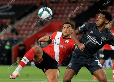 Southampton's Che Adams, left, duels for the ball with Brentford's Dominic Thompson during the English League Cup soccer match between Southampton and Brentford at St. Mary's Stadium in Southampton, England