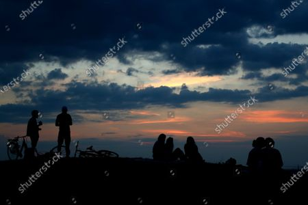 Stock Photo of Young people enjoy the view from a hill as the sun sets at the Olympic park in Munich, Germany, Wednesday, Sept.16, 2020