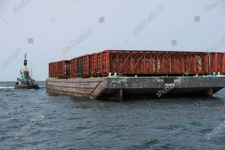 Stock Image of In this photo provided the Office of Governor Andrew M. Cuomo, old rail cars sit on a barge near where they are to be dumped into the ocean a few miles off shore from Point Lookout, N.Y., . The debris will be used to create an artificial reef that will attract fish and other marine life