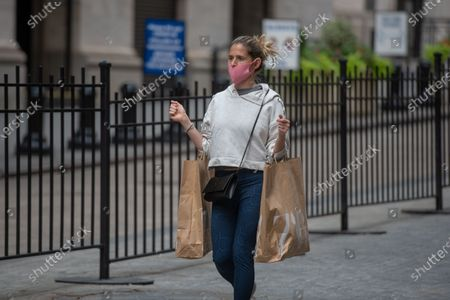 A woman holds shopping bags as she walks past the New York Stock Exchange (NYSE) on Wall Street