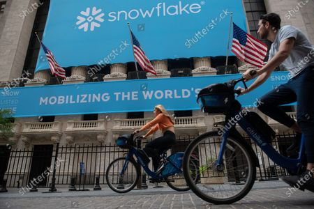 People on bicycles rides past the New York Stock Exchange (NYSE) on Wall Street as a banner announcing the IPO of Snowflake, a data storage provider, hangs outside.