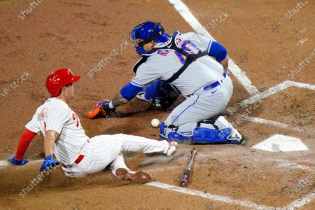 Philadelphia Phillies' Scott Kingery, left, scores past New York Mets catcher Wilson Ramos on a fielder's choice hit into by Andrew McCutchen during the second inning of a baseball game, in Philadelphia. McCutchen was safe at first on the play