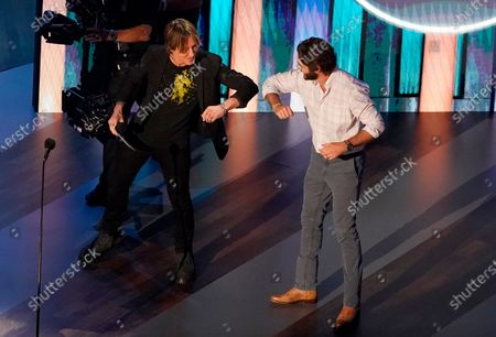 Thomas Rhett, right, winner of the entertainer of the year award, elbow bumps host Keith Urban on stage during the 55th annual Academy of Country Music Awards at the Grand Ole Opry House, in Nashville, Tenn