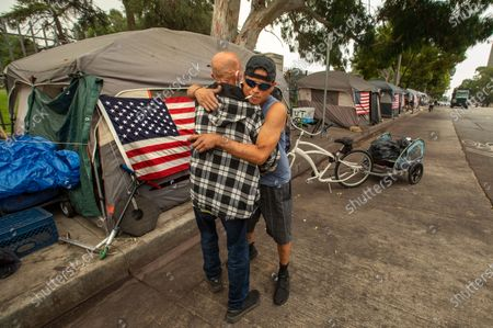 Stock Image of Navy veteran Ryan Higgins, 46, right, greets Navy veteran Michael Miller, 65, outside Higgins' tent at a homeless encampment for veterans on San Vicente Blvd. in Brentwood, the hometown of VIce Presidential candidate Kamela Harris. Higgins said that he has resided at this homeless encampment for over 5 years. (Mel Melcon / Los Angeles Times)