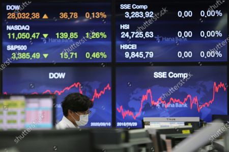 Currency trader watches monitors at the foreign exchange dealing room of the KEB Hana Bank headquarters in Seoul, South Korea, . Asian stock markets declined Thursday after the U.S. Federal Reserve indicated its benchmark interest rate will stay close to zero at least through 2023 but announced no additional stimulus plans