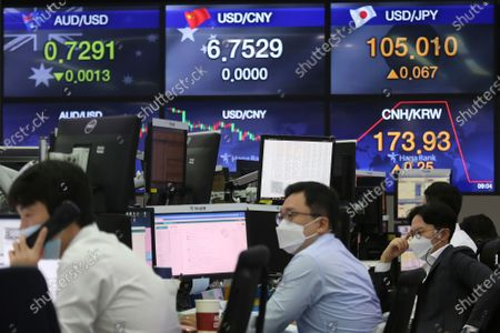 Currency traders work at the foreign exchange dealing room of the KEB Hana Bank headquarters in Seoul, South Korea, . Asian stock markets declined Thursday after the U.S. Federal Reserve indicated its benchmark interest rate will stay close to zero at least through 2023 but announced no additional stimulus plans