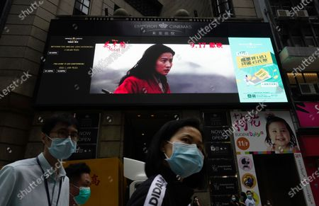 "Stock Picture of People walk past a huge TV screen showing movie ""Mulan"" at a downtown street in Hong Kong . The remake of ""Mulan"" struck all the right chords to be a hit in the key Chinese market. Disney cast beloved actresses Liu Yifei as Mulan and removed a popular dragon sidekick in the original to cater to Chinese tastes"