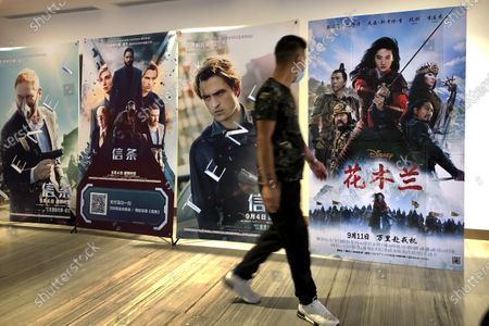 "Man wearing a face mask walks past a poster for the Disney movie ""Mulan"" at a movie theater in Beijing, on . The remake of ""Mulan"" struck all the right chords to be a hit in the key Chinese market. Disney cast beloved actresses Liu Yifei as Mulan and removed a popular dragon sidekick in the original to cater to Chinese tastes"