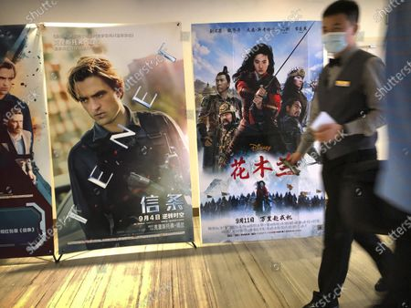 "An employee wearing a face mask walks past a poster for the Disney movie ""Mulan"" at a movie theater in Beijing on . The remake of ""Mulan"" struck all the right chords to be a hit in the key Chinese market. Disney cast beloved actresses Liu Yifei as Mulan and removed a popular dragon sidekick in the original to cater to Chinese tastes"