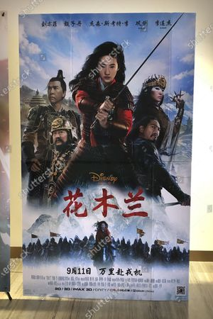 "Stock Image of Poster for the Disney movie ""Mulan"" is displayed at a movie theater in Beijing on . The remake of ""Mulan"" struck all the right chords to be a hit in the key Chinese market. Disney cast beloved actresses Liu Yifei as Mulan and removed a popular dragon sidekick in the original to cater to Chinese tastes"